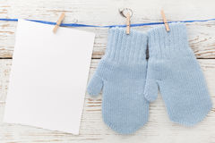 Small baby gloves, blank card on white wooden background. Flat lay. Top view Royalty Free Stock Photos