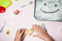 Small baby hands mold the heart from a homemade dough. Smiley on a tray of flour royalty free stock photography