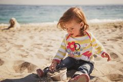 Small baby, little girl in blue jeans, pink shoes and colourful pullover sitting and playing in sand at the beach. With big dog behind Royalty Free Stock Photos