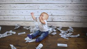Baby and a lot of money on the floor. A small baby and a lot of money on the floor stock footage