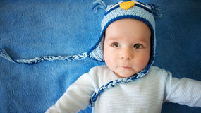 Small baby in owl hat on blue background Royalty Free Stock Image