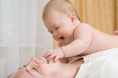 Small baby, playing with mother Stock Images