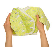 Small baby's undershirt in the female hands Royalty Free Stock Image