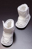Small baby shoes. White shoes with heart and wings for baby royalty free stock photo