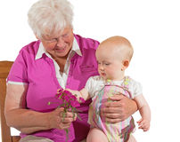 Small baby sitting contentedly with Grandma Stock Photo