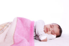 Small baby sleeping under a colorful blanket Stock Photo