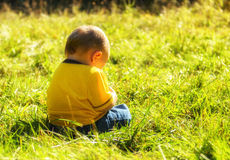 Solitude. A small baby or toddler sitting in the grass during late afternoon with his/her back facing the camera stock photos