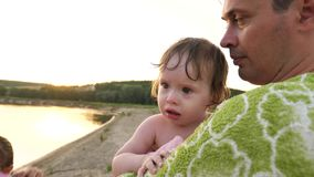 Small baby was upset and crying dropping tears in hands of dad wrapped in towel on city beach.  stock footage
