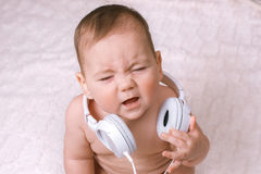 Small baby wearing earphones crying Stock Photo