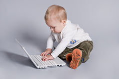 Small baby with white laptop Stock Image