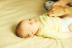 Mom wearing diaper. Small baby in yellow shirt lying on bed and mother wearing him diaper stock photo