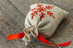 Small bag with a gift. Small bag with a red ribbon on a wooden board Stock Photo