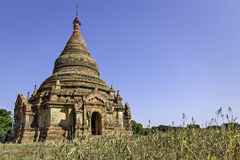 Small Bagan Temple. Brick Buddhist temple with conical roof seen from ground level against blue sky with grass in foreground stock images