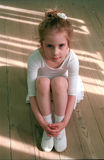 The small ballerina. The young dancer in a white dress sits on a floor after a lesson stock photos