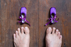 Small ballet shoes and big feet Royalty Free Stock Images