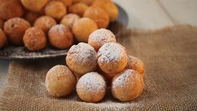 Small balls of freshly baked homemade cottage cheese doughnuts on the jute napkin. Woman`s hand pouring icing sugar. Small balls of freshly baked homemade stock video footage