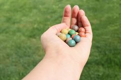 Small balls for playing marbles in hand of woman isolated on green bokeh background royalty free stock photos