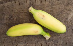 Small bananas on an old wood board Royalty Free Stock Photos