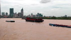 Small barges head towards Ho Chi Minh City. Small boats travel on the muddy Saigon River in Vietnam, heading towards Ho Chi Minh City. The skyscrapers of the stock footage