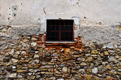 Small barred window. In stone wall Royalty Free Stock Photos