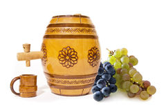 Small barrel with grapes. Small decorative wooden barrel with wooden cup and grapes on white background Royalty Free Stock Images