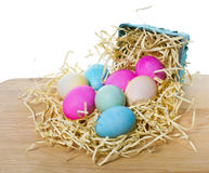 Small basket with colorful eggs spilling out Royalty Free Stock Photography