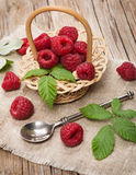 Small basket with fresh raspberries on wooden background. Sweet raspberries in basket  on the wooden table Royalty Free Stock Photography