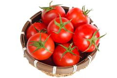 Small basket full of red tomatoes. Isolated red tomatoes in the small basket on the white background Stock Photos