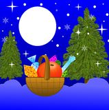 Small basket with gifts on to snow in-field Royalty Free Stock Images