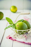 Small basket with limes and mint leafs Royalty Free Stock Photos