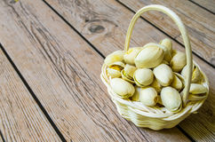 Small basket of pistachios. Pistachio nuts in a small white basket Stock Photo