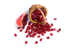 Small basket with pomegranate seeds. !Small basket with scatter pomegranate seeds on white background Royalty Free Stock Image