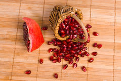 Small basket with pomegranate seeds on rug. Small basket with scatter pomegranate seeds and peace of pomegranate on wood rug Stock Photo