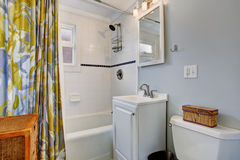 Small bathroom with blue walls, and colorful shower curtain. Stock Images