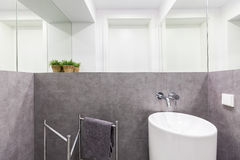 Small bathroom with modern sink. Simple small bathroom with gray granite walls, white modern sink and wall mirrors stock image