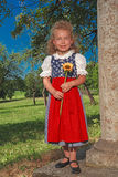 Small Bavarian girl in a dirndl with sunflower Stock Photos