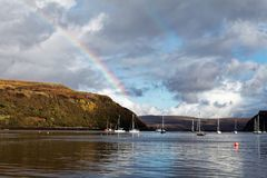Small bay with boats and rainbow stock photography