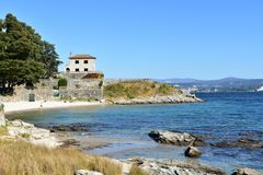 Small beach with rocks, trees and turquoise water. House on the hill, bright sand, sunny day. Blue sky. Galicia, Spain. royalty free stock photos