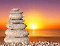 Small beach zen stone with sun down background close up for spa. And balance symbol Stock Photography