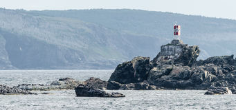 Small beacon lightstation on rocks in Bona Vista proper beach, Newfoundland. Stock Photos