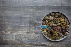 Small beads on wooden background. Bunch of small beads into tin lid on wooden background Royalty Free Stock Photo