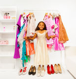 Small beautiful African girl choosing clothes. Small beautiful African girl standing between hangers with colorful bright dresses, clothes and high heels on the royalty free stock image