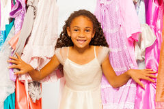 Small beautiful African girl stands among clothes. Small beautiful African girl close-up view standing between hangers with colorful bright dresses, clothes royalty free stock photos