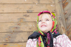 The small beautiful angry girl in a scarf. At a fence looks upward with a smile Stock Photography