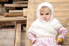 The small beautiful angry girl in a white scarf. At a fence Stock Photo
