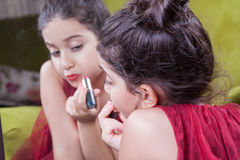 Small beautiful arab middle eastern girl with pretty red dress and lips doing makeup carefully at home in mirror. 8-10 years. Royalty Free Stock Photo
