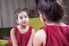Small beautiful arab middle eastern girl with pretty red dress and lips posing and looking at herself in mirror. 8-10 years. Royalty Free Stock Photos