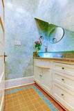Small beautiful blue bathroom, powder room with blue sink and white cabinets. Tulips near sink Stock Images