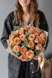 Flowers coffee color, cappuccino roses with eucalyptus. Small Beautiful bouquets in woman hand. Floral shop concept royalty free stock photos