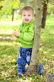 The small beautiful boy walks on a green glade with an apple Royalty Free Stock Photo